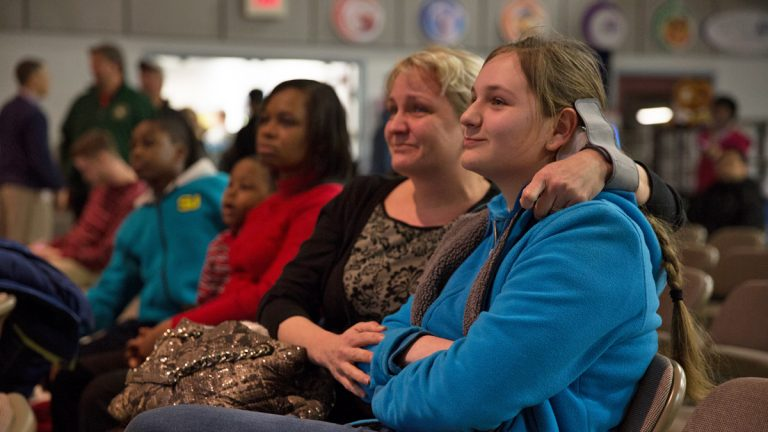 Anastasia Ratkova (center) becomes emotional as her daughter, Nicole, 14, is named first on the 9th grade waiting list at MaST Community Charter School.  (Lindsay Lazarski/WHYY)