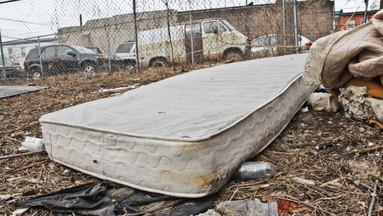 A mattress sits  among litter in a South Philadelphia lot. (Kimberly Paynter/WHYY)