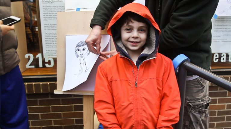 Max Perlman, 8, spends first Fridays drawing dollar portraits of art lovers outside the Arden Theater in Old City, Philadelphia. (Kimberly Paynter/WHYY)