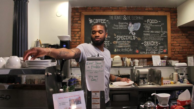 Naje Taylor works as a barista at The Monkey & The Elephant cafe in Brewerytown. (Emma Lee/WHYY)