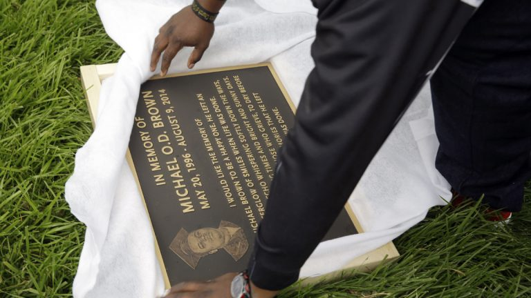 Michael Brown Sr. is shown unwrapping a plaque memorializing his son, Michael Brown in Ferguson, Missouri. (AP Photo/Jeff Roberson, file)