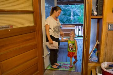 """Michelle Andrews helps her son, Gabriel, into the house after playing in the backyard. She is one of three women Keystone Crossroads' reporter Marielle Segarra followed for the story, """"At Allentown's Turner Street program, insight into what homeless families need."""" Listen here: http://bit.ly/2dRsU4A (Lindsay Lazarski/WHYY)"""