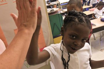 Mifflin Principal Leslie Mason delivers a high five to first-grader Daiyanah Gibson for learning to count. (Kimberly Paynter/WHYY)