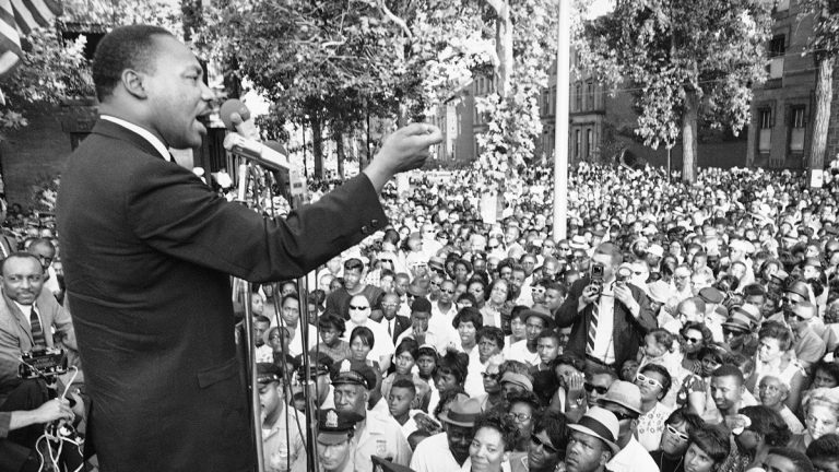 Dr. Martin Luther King is shown speaking at a amass meeting in front of all-white Girard College in Philadelphia on  August 4