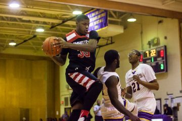 Imhotep's Deante Robinson grabs a rebound in Thursday's game agains northwest rival Martin Luther King High School. (Brad Larrison/for NewsWorks)