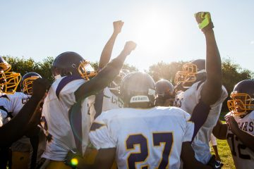 The MLK Cougars celebrate their first win of the season against John Bartram High School. They would go on to win the rest of their regular season games. (Brad Larrison/for NewsWorks)