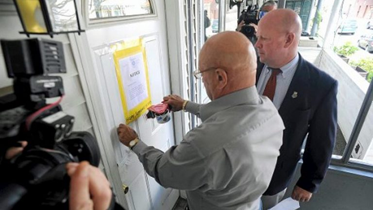 Wilkes-Barre City Code Enforcement Officer Frank Kratz, (left), and Mayor Tom Leighton post a closure notice (Mark Moran/The Citizens' Voice)
