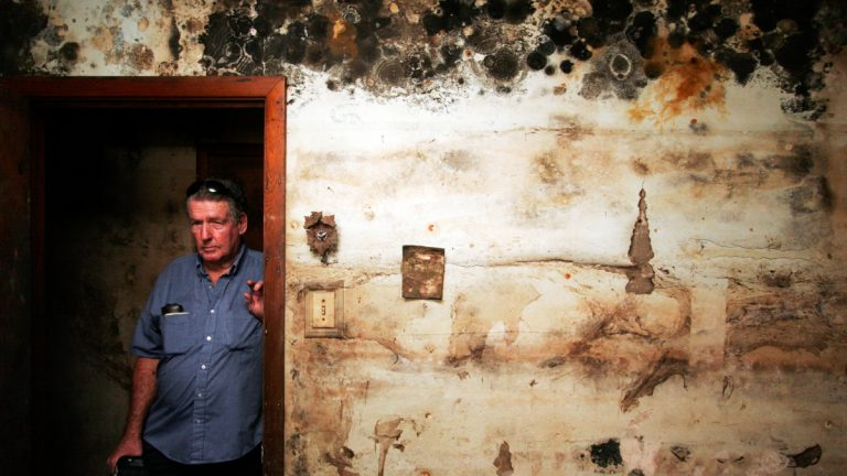 Joe Middleton poses for a photograph in his still yet-to-be gutted home