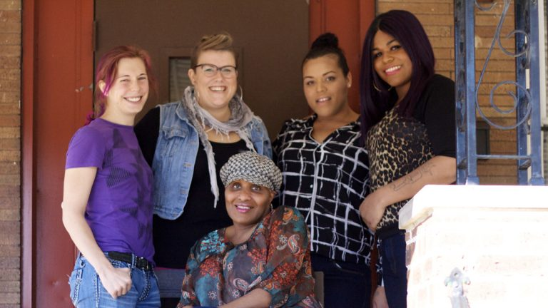 Residents and staff on the porch of the Morris Home, located in Southwest Philadelphia. From left are Kai; Program Director Laura Sorensen; Nikki; Lauren; and Barbie, center. (Kyrie Greenberg/for NewsWorks)