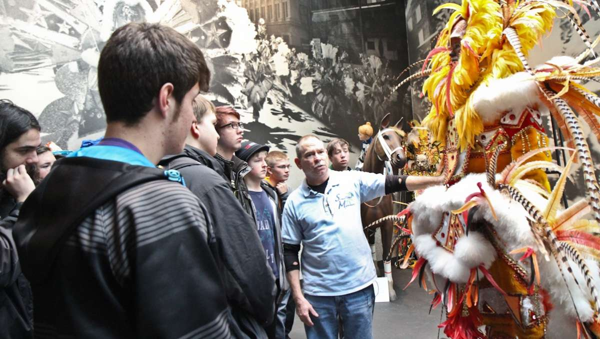 Students from the Arapahoe High School band learn about the cost of ostrich feathers at Philadelphia's Mummers Museum on Monday. (Kimberly Paynter/WHYY)