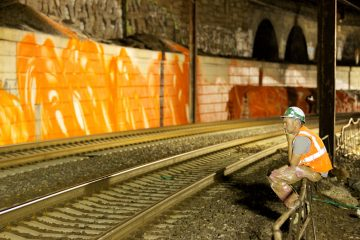 German artist Arne Schreiber observes progress to a major public art installation along the rail tracks outside of 30th Street Station and the Schuylkill Expressway in Philadelphia, Pa.  (Nathaniel Hamilton/For NewsWorks)