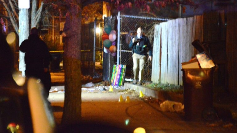 Wilmington Police search for clues Monday night after a city man was killed in front of a memorial to a shooting victim who was killed Friday night. (John Jankowksi/for NewsWorks)
