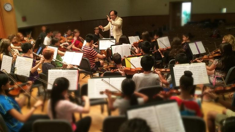 Simeone Tartaliogne, music director for the Delaware Youth Symphony Orchestra, teaches children at the Music School of Delaware. (Zoe Read/WHYY)