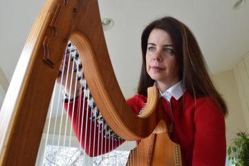 Jennifer Hollis tunes her harp before playing for palliative care patients. (Paige Pfleger/WHYY)