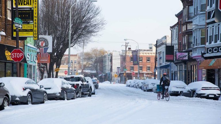 A cyclist bikes through the Queen Village neighborhood of Philadelphia after six to 10 inches of snow fell overnight. (Lindsay Lazarski/WHYY)