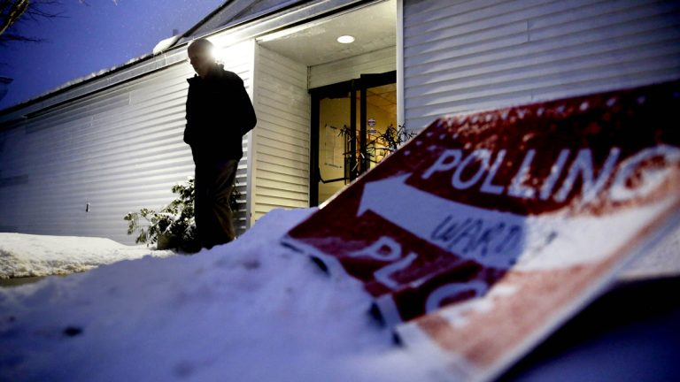 A voter leaves a polling site at dawn after casting a ballot. (AP Photo/David Goldman)