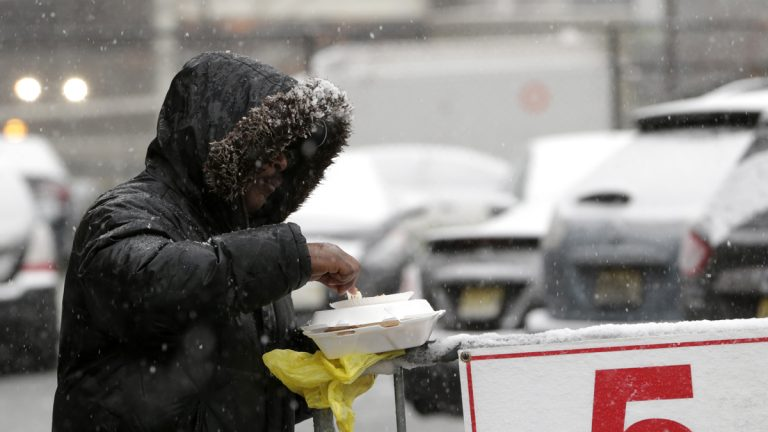 Snow falls over a homeless person in Newark