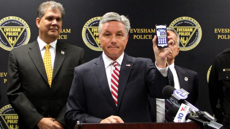 Evesham Township Mayor Randy Brown holds up a smart phone with the Uber app. A new program provides free rides for residents leaving bars and restaurants in the township. (Emma Lee/WHYY)