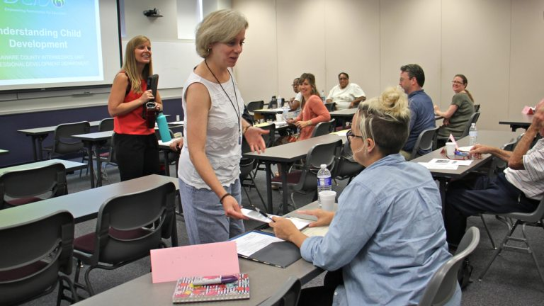 Professional development specialist Nora Connell hands out materials during a class for prospective substitute teachers at Delaware County Intermediate Unit. (Emma Lee/WHYY)