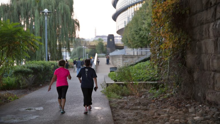 People walk on the North Shore Trail along the Allegheny River in Pittsburgh, Pa. (Lindsay Lazarski/WHYY)