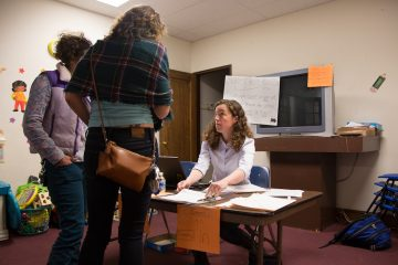 Hillary for President volunteer, Michelle Dorothy, from Virginia, checks in new canvasers before sending them to a quick training at a Get Out The Vote center in North Philadelphia. (Emily Cohen for NewsWorks)