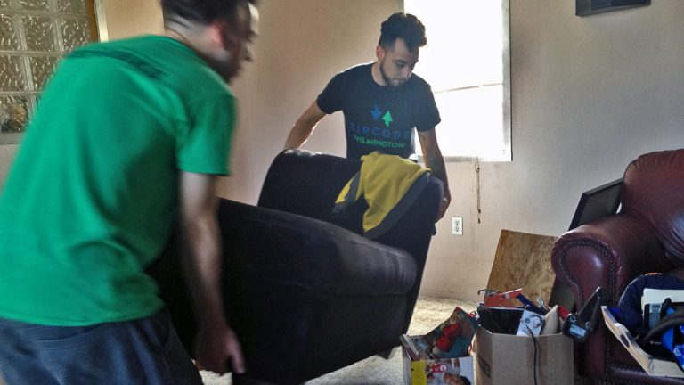 Joel Guevara (right) moves a chaise longue into his new apartment. (Avi Wolfman-Arent/WHYY)