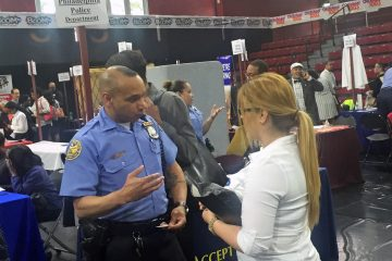 Officer Samuel Cruz with the Philadelphia Police Department's recruiting division chats with a would-be recruit at a job fair at Temple University.(Bobby Allyn/WHYY)