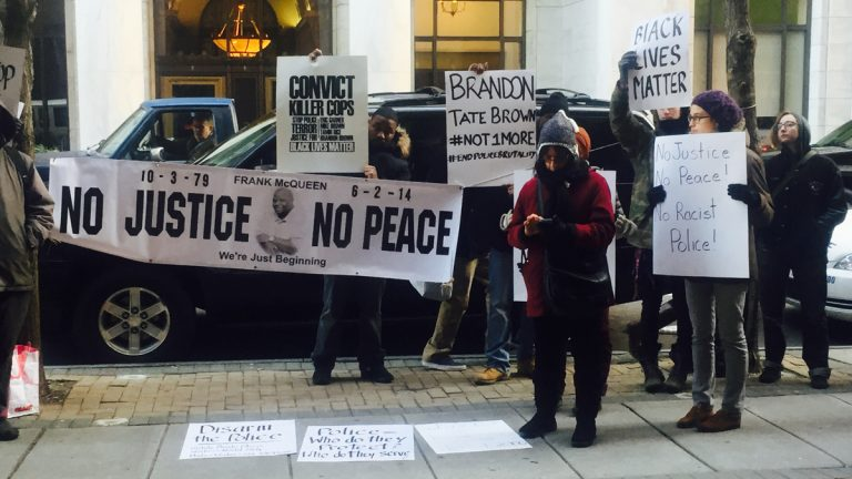 Protesters in January calling for more answers in the fatal December shooting of Brandon Tate-Brown. The group assembled outside of an event in which U.S. Attorney General Eric Holder met with city leaders for a roundtable about community relations with police. (Bobby Allyn/WHYY)