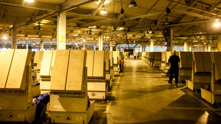 Workers prepare voting machines at the Office of the  City Commissioner's warehouse the day before the recount of votes in 75 precincts was set to begin. (Brad Larrison for NewsWorks)