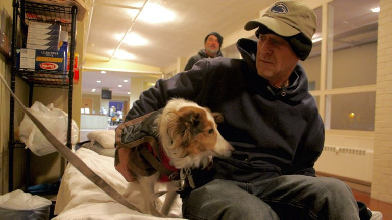 Greg Crockenberg settles in at the Code Blue - and now Code White - shelter at Woodside Church with his dog Sarah. (Emma Lee/WHYY)