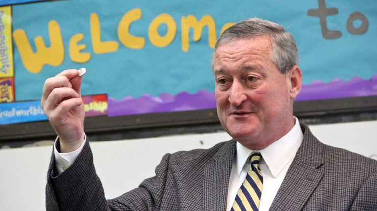 Jim Kenney holds up a SEPTA token, saying that continuing to use  public transit is one of the ways he will keep in touch with his constituency. (Emma Lee/WHYY)