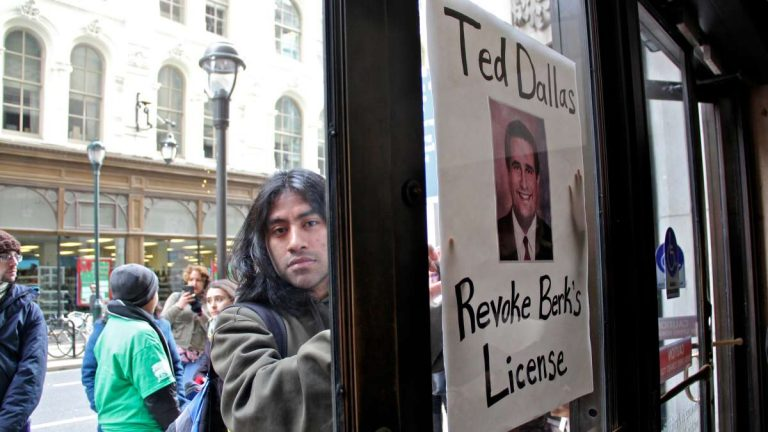 Juntos volunteer Drew Morrissey presses his poster against the door at 801 Market St. after he and other protesters were asked to leave the building. Ted Dallas is the Pennsylvania Secretary of Human Services. (Emma Lee/WHYY)