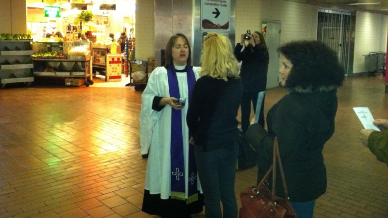 Pastors from St. Peter's Church distribute ashes at Market East Station on Ash Wednesday in Philadelphia as part of Ashes to Go, a nationwide initiative (Eugene Sonn/WHYY)
