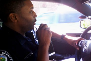 A Camden County police officer on the radio in a squad car. (NewsWorks file photo)