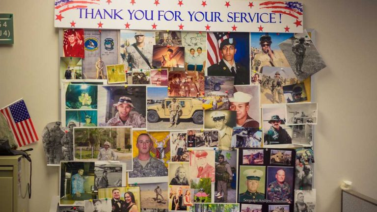 Photos of veterans hang on the wall at the Vets4Warriors suicide prevention hotline center at Rutgers University Behavioral Health Services in Piscataway, New Jersey. (John Abbott/for NewsWorks)