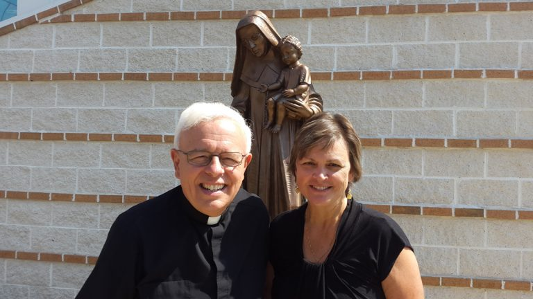 Monsignor John Marine and parishioner Kathy Nachtman stand in front of a statue of St. Katharine Drexel outside of St. Bede's parish. (Laura Benshoff/WHYY)