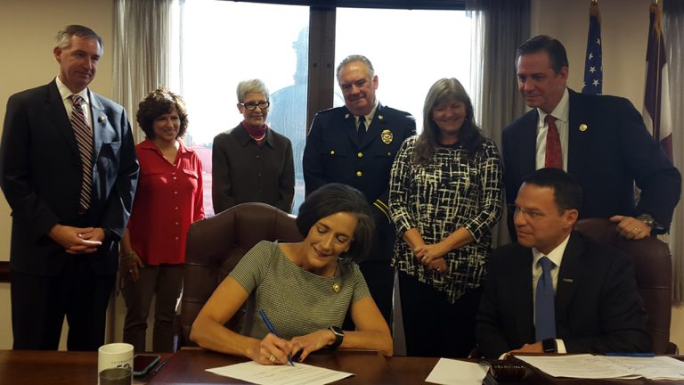 Montgomery County Commissioner Val Arkoosh signs the standing order to allow pharmacies to dispense naloxone without a prescription. (Laura Benshoff/WHYY)