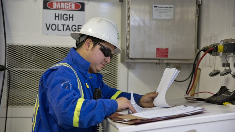 A worker checks paperwork on the monkey board of a Cabot Oil & Gas drill rig in Kingsley, Pa.  (Lindsay Lazarski/WHYY)