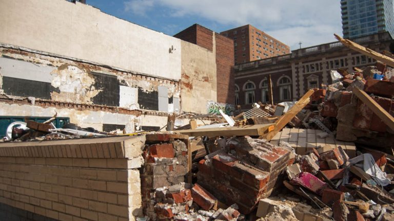 A piece of wall holds back some of the rubble from the 2013 collapse. (Lindsay Lazarski/WHYY)