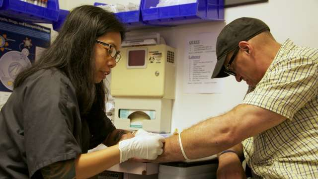 A phlebotomist takes blood for Hepatitis C testing during a patient's weekly visits (Nathaniel Hamilton/for Newsworks)