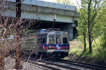 A SEPTA Regional Rail train passes under a bridge.
