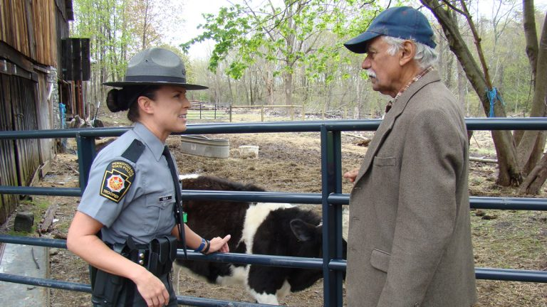Dr. Shankar Shastri (right) talks with Pa. State Trooper Carie Gula after the people who dumped a severed cow head at his bovine sanctuary were charged. (Ramaa Reddy Raghavan/for NewsWorks)