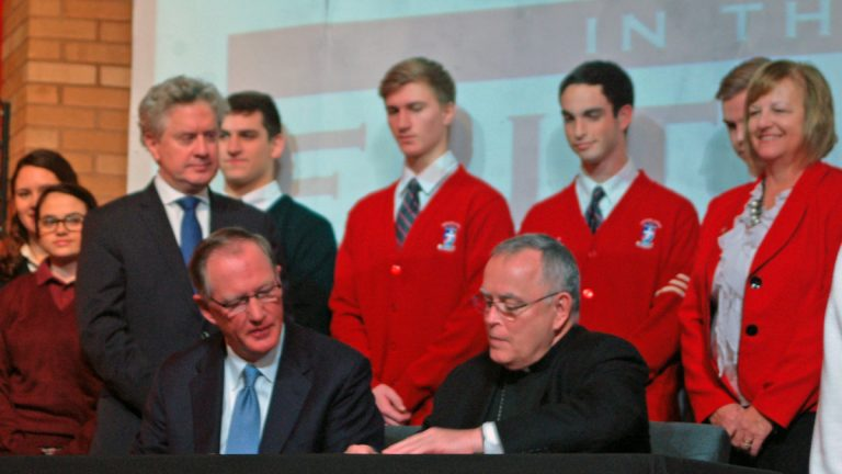 At Archbishop Ryan High School in Philadelphia, Faith in the Future board chairman Ed Hanway, left,  and Archbishop Charles Chaput sign the management agreement. (Sara Hoover/for NewsWorks)