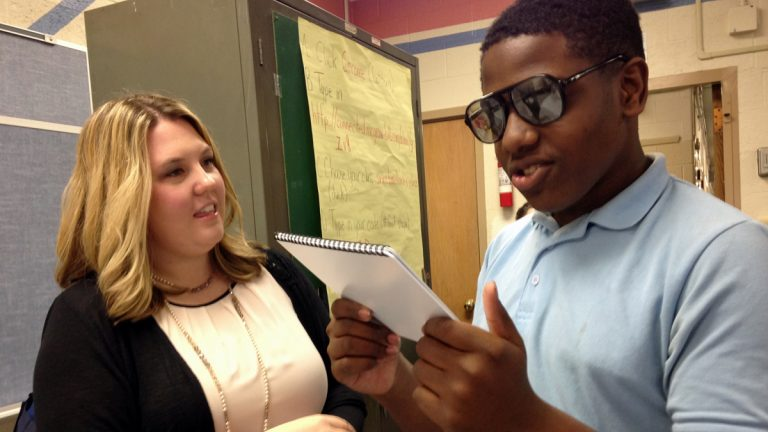 Meghan Mattson shows a seventh-grader at Alexander Adaire School in Fishtown vision-impairing glasses that simulate post-concussion symptoms.(Todd Bookman/WHYY)