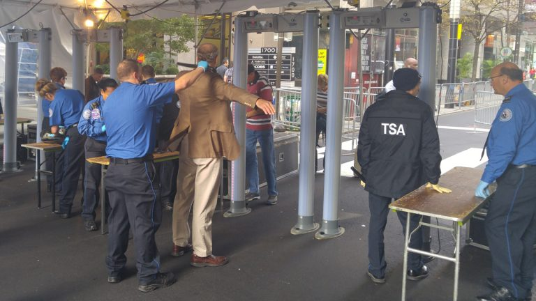 TSA agents wand people passing through metal detectors at 17th and Market Streets in Philadelphia (Tom MAcDonald/WHYY)