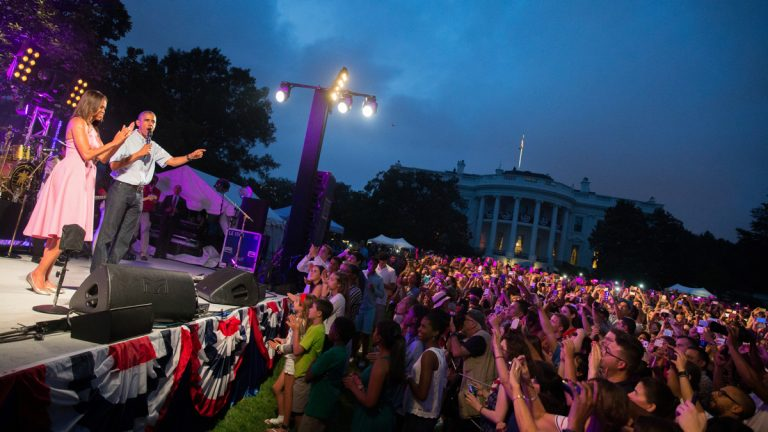 President Barack Obama, accompanied by first lady Michelle Obama, delivers remarks during an Independence Day celebration on the South Lawn at the White House in Washington, Saturday, July 4, 2015. (AP Photo/Andrew Harnik)