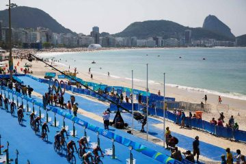 Competitors ride through the transition area during the men's triathlon event along Copacabana beach at the 2016 Summer Olympics in Rio de Janeiro