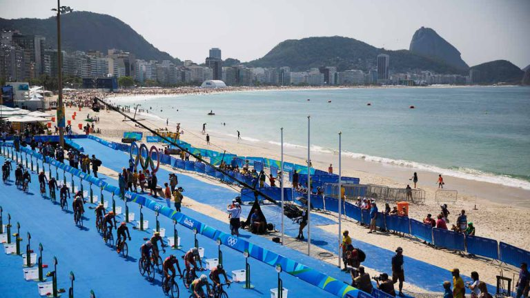 Competitors ride through the transition area during the men's triathlon event along Copacabana beach at the 2016 Summer Olympics in Rio de Janeiro