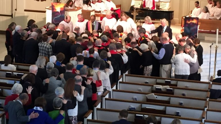 Church leaders lay hands on Kaci and Holly Clark Porter during an ordination service Sunday afternoon in Wilmington. (Paul Parmelee/WHYY)