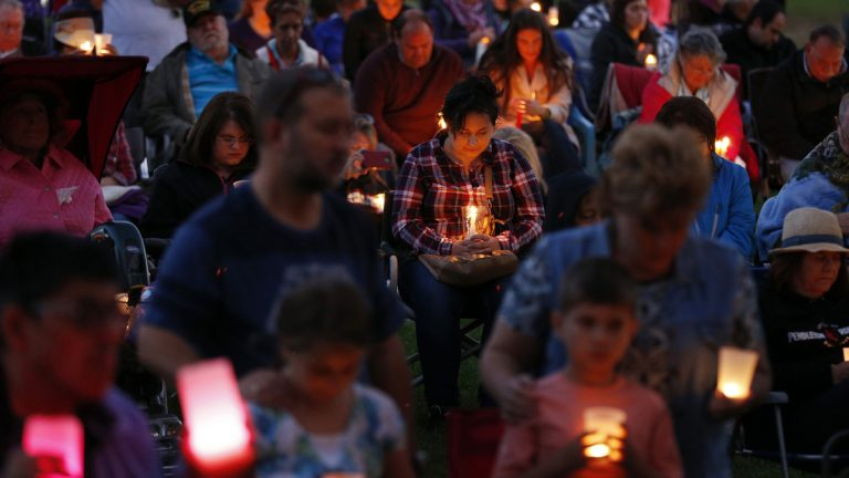People bow their heads in prayer during a prayer vigil Saturday, Oct. 3, 2015, in Winston, Ore. The vigil was held in honor of the victims of the fatal shooting at Umpqua Community College on Thursday. (AP Photo/John Locher)